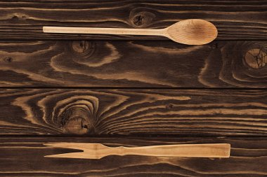 elevated view of wooden fork for meat and spoon on table