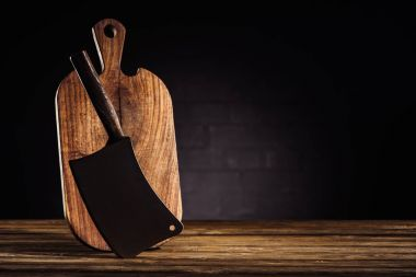 closeup view of wooden cutting board and butcher axe on table
