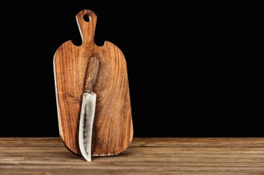 closeup view of knife and wooden cutting board on black background