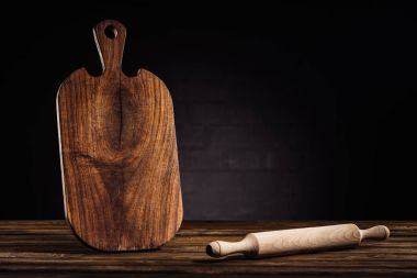 closeup shot of rolling pin and wooden cutting board on table