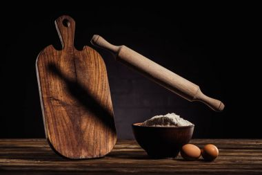flying rolling pin, wooden cutting board, two eggs and bowl with flour on table