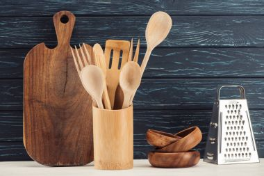 closeup shot of cutting board, kitchen utensils, grater and ramekins in front of wooden wall