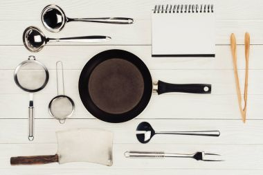 top view of blank textbook, frying pan, butcher axe and kitchen utensils on white wooden table