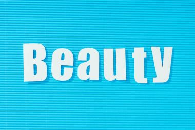 white word beauty on bright blue striped background, beauty concept