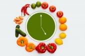 Fotografia vista superiore del cerchio di frutta e verdura con orologio verde interno isolato su bianco