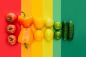 pohled shora zralých rajčat, citróny a okurky na barevný povrch