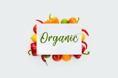 top view of sheet of paper with text Organic on vegetables and fruits isolated on white
