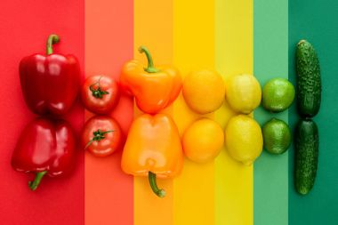 top view of ripe fruits and vegetables on rainbow surface