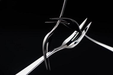 three forks with two tines isolated on black