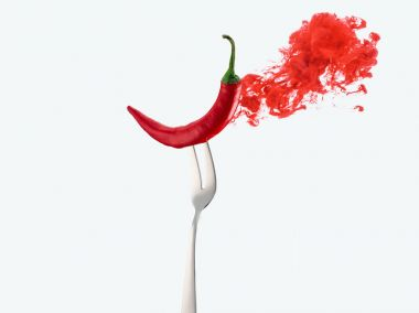 red chili pepper on fork and red ink isolated on white