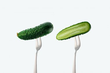 cut and whole cucumbers on forks isolated on white