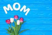 Fotografia vista superiore del bouquet di tulipani rosa e bianchi e la parola mamma sul tavolo blu, concetto di giorno di madri