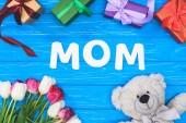 felülnézet díszdobozok, maci, tulipánok és word anya a kék tábla, anyák napi koncepció