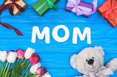 top view of gift boxes, teddy bear, tulips and word mom on blue table, mothers day concept