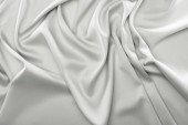 Photo close up view of folded grey silk fabric as backdrop