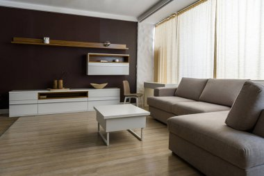 Light room interior with grey sofa and table