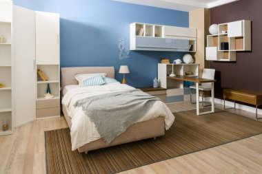 Bedclothes on bed in cozy bedroom in blue tones