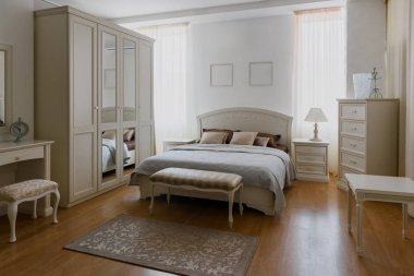 Light linen on bed in elegant bedroom with mirror
