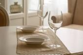 Weingläser und weiße Teller auf dem Tisch im Esszimmer