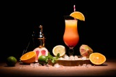 Fotografie alcohol cocktail with orange juice on wooden board with fruits on table
