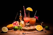 schmackhafte Alkohol Cocktails auf Holzbrett mit Früchten auf Tisch
