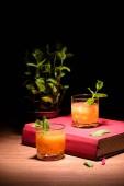 Alkohol Cocktails mit Minze auf rosa Buch auf Tisch