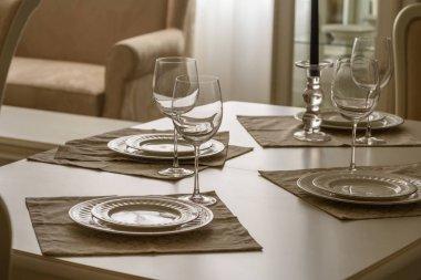 Set of dinner tableware on table in dining room