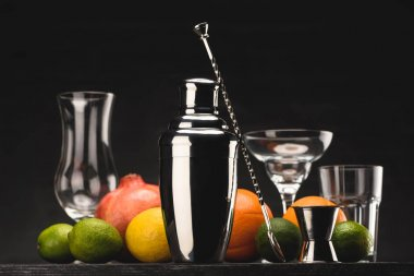 shaker for preparing alcohol drink and empty glasses on table isolated on black