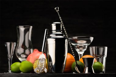 shining shaker for preparing alcohol drink, empty glasses and ripe fruits on table isolated on black