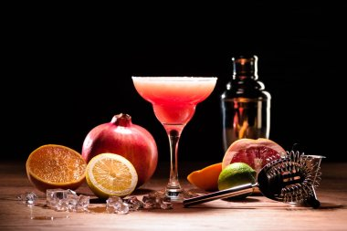 red alcohol margarita drink with fruits on wooden table