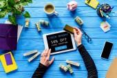 Hände halten Tablet und Kreditkarte auf blauen Holztisch mit Geld, Cyber Montag, kostenloser Versand Schriftzug