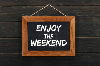blackboard with enjoy the weekend inscription hanging on wooden wall