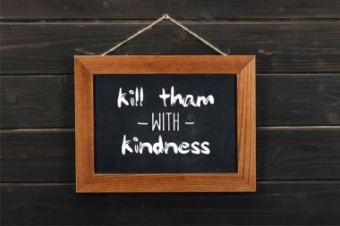 blackboard with kill tham with kindness inscription hanging on wooden wall