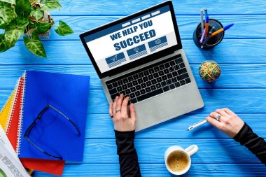hand typing on laptop keyboard on blue wooden table with stationery and coffee, We help you succeed lettering