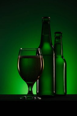 close up view of bottles and glass of beer on dark green background