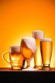 pohled připravené hrnky studené pivo s pěnou na oranžové pozadí na plochu
