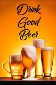pohled na připravené hrnky studené pivo s pěnou a pití dobré pivo nápis na oranžové pozadí na plochu