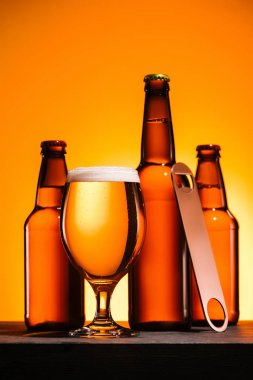 close up view of bottles, glass of beer with foam and bottle opener on orange background