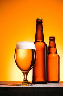 close up view of bottles and glass of beer with foam on surface on orange background