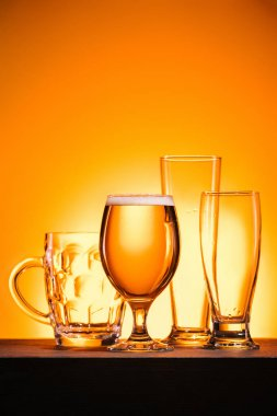 close up view of arranged empty glasses and mug of beer on orange background