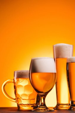 close up view of arranged mugs of cold beer with froth on orange background
