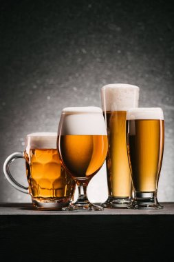 close up view of arranged mugs of beer on grey background
