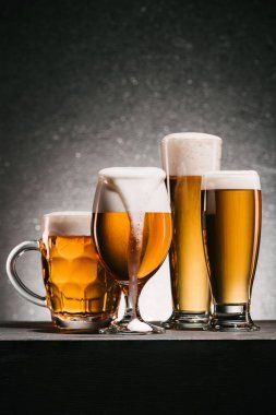 close up view of mugs of cold beer with foam on grey background