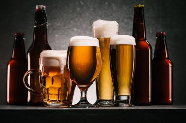 close up view of bottles and mugs of beer with froth on grey background