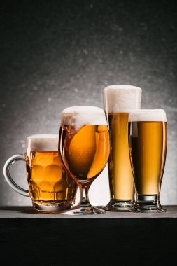 close up view of mugs of beer with froth on grey background