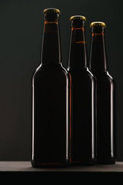 close up view of arranged bottles of beer on dark backdrop