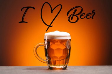 close up view of mug of cold beer and i love beer lettering on orange backdrop