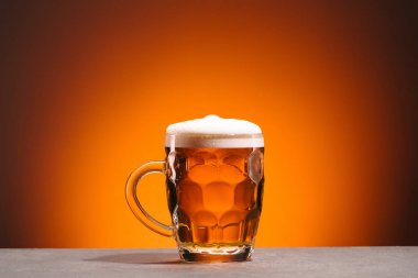 close up view of mug of cold beer on orange backdrop