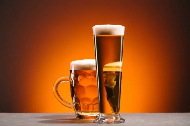 close up view of arrangement of glasses of beer with froth on orange backdrop