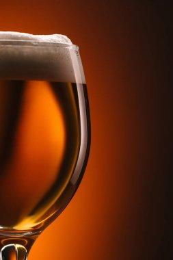 close up view of mug of beer on orange backdrop